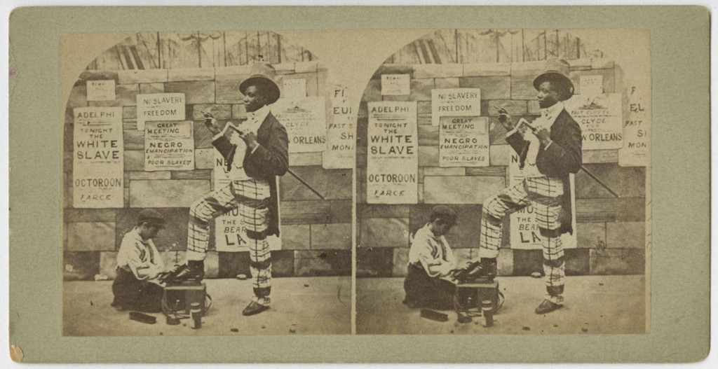 Satiric stereograph showing an African American dandy receiving a shoe shine from a white shoe shine boy