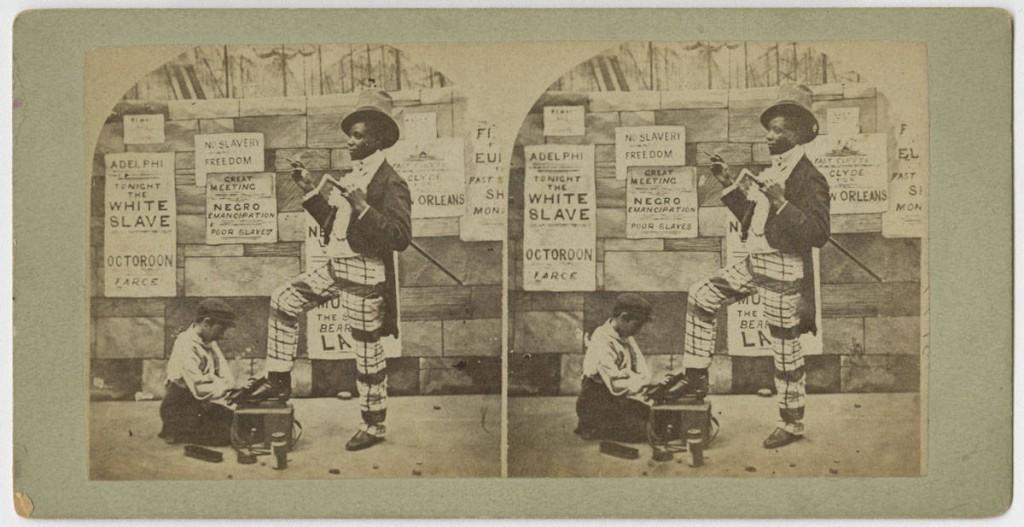 Satiric stereograph showing an African American dandy receiving a shoe shine from a white shoe shine boy